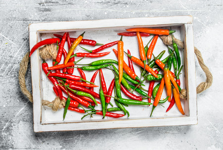 Spicy flavorful pepper on the tray. On rustic background 写真素材
