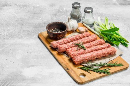 Raw beef sausages with garlic and herbs. On a rustic background. Imagens