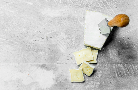 Brie cheese with knife. On a rustic background.
