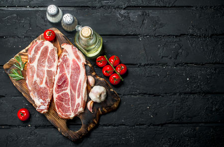 Raw pork steaks with aromatic and herbs and spices. On a black rustic background. Stock Photo