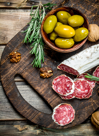 Salami with olives and a sprig of rosemary. On a wooden background. Banco de Imagens