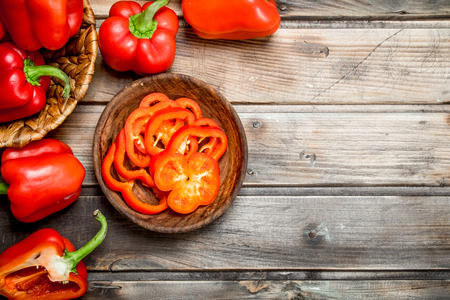 Pieces of sweet pepper in a bowl and a whole pepper in a basket. On wooden background