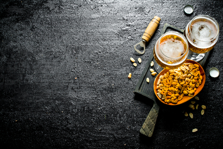 Two glasses of beer and peanuts in a bowl on a black cutting Board. On black rustic background