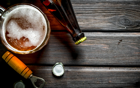 Beer and opener with a cover. On black wooden background 免版税图像