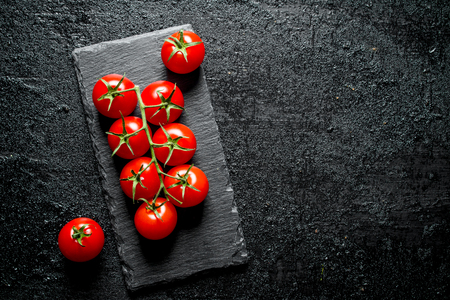 Tomatoes on a stone Board. On black rustic background