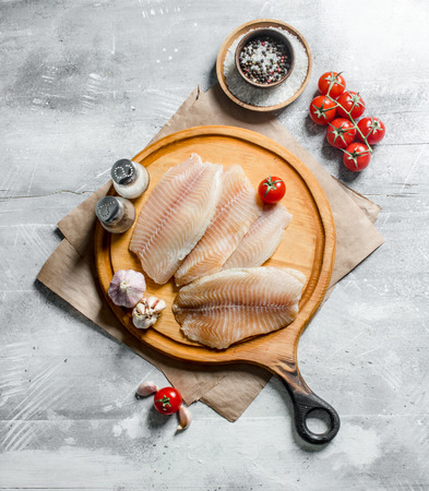 Fish fillet on a round cutting Board with spices, tomatoes and garlic. On white rustic background