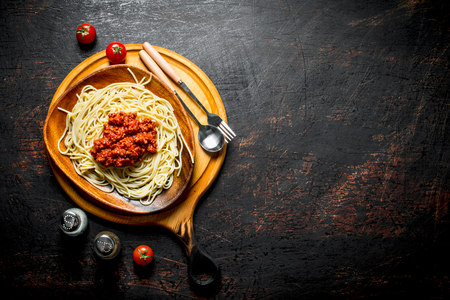 Pasta with Bolognese sauce in a wooden bowl with spices. On rustic background