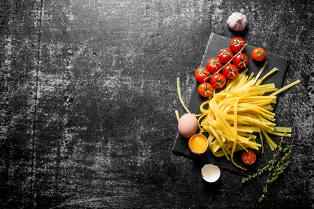 Homemade raw pasta with eggs, tomatoes and garlic on a stone Board. On rustic background