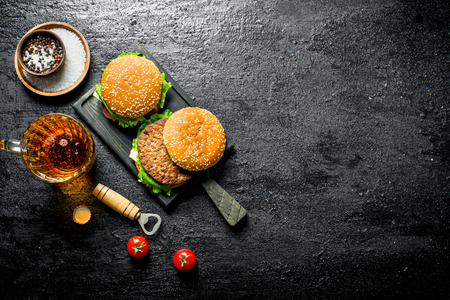 Burgers with beer in a glass and tomatoes. On black rustic background