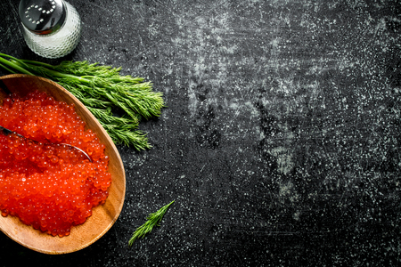 Red caviar in a bowl with salt and dill. On black rustic background