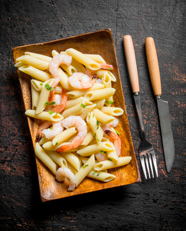 Pasta with shrimp on a wooden plate with a knife and fork. On dark rustic background Reklamní fotografie
