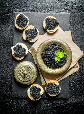 Sandwiches with black caviar and caviar in a bowl on paper with parsley. On black rustic background
