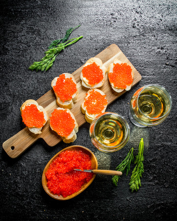 Sandwiches with red caviar on a cutting Board and white wine in glasses. On black rustic background