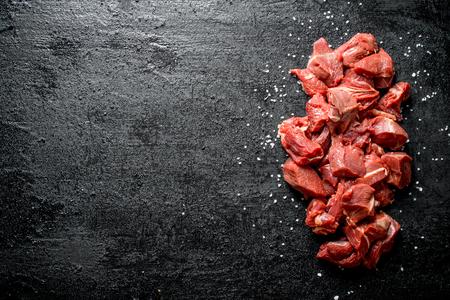Sliced raw beef with salt grains. On black rustic background Standard-Bild - 121035625