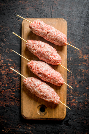 Raw kebab of ground beef on a wooden cutting Board. On rustic background