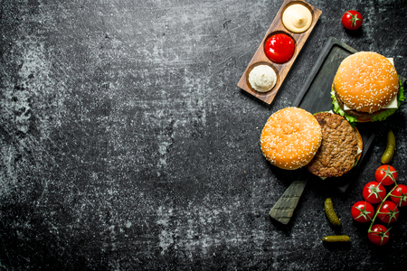 Burgers with French fries, gherkins,tomatoes and different sauces. On rustic background
