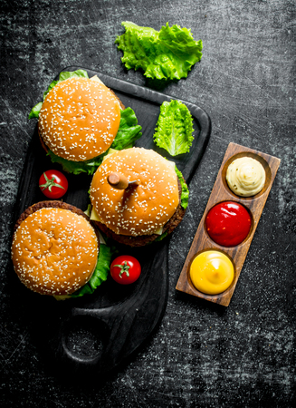 Burgers with salad leaves,tomatoes and sauces. On black rustic background 版權商用圖片