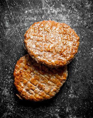 Two cooked cutlets. On rustic background