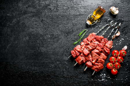 Raw kebab on skewers with tomatoes, garlic and oil in a bottle. On black rustic background Zdjęcie Seryjne