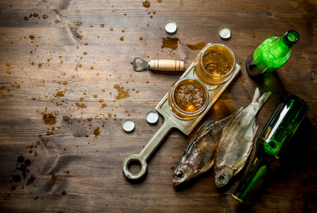 Glasses of beer on a stand and dried fish. On wooden background Фото со стока