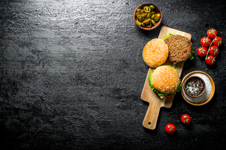 Burgers with jalapeno chillies and tomatoes. On rustic background