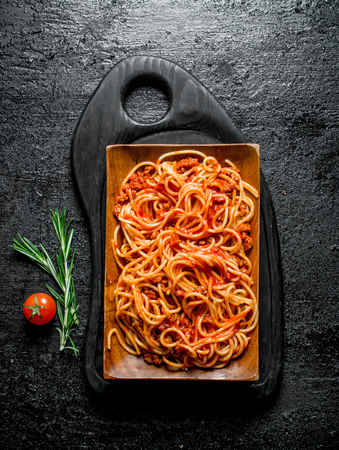 Pasta with Bolognese sauce in the plate with rosemary and tomato. On black rustic background Imagens