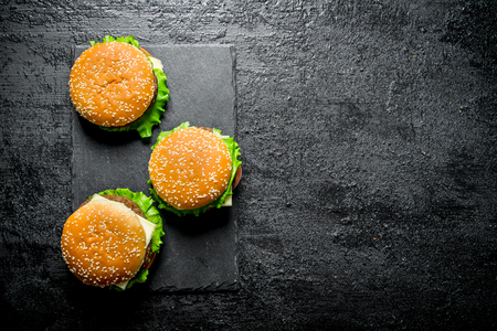 Burgers with beef,vegetables and cheese. On black rustic background Stock Photo