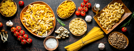 Assortment of different types of raw pasta with mushrooms, tomatoes and garlic. On dark rustic background