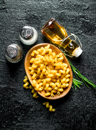 Raw paste in bowl with rosemary, spices and oil in bottle. On black rustic background 版權商用圖片
