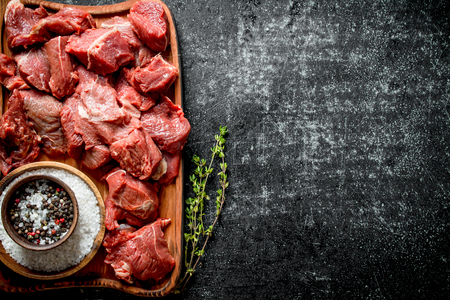 Sliced raw beef on a cutting Board with thyme and seasonings in bowls. On black rustic background Reklamní fotografie