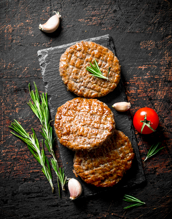 Cutlets on a black stone Board with pieces of garlic,rosemary and cherry. On dark rustic background Stock fotó