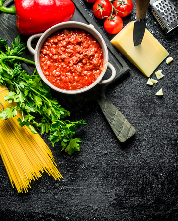 Bolognese sauce in a pan with dry pasta and cheese. On black rustic background