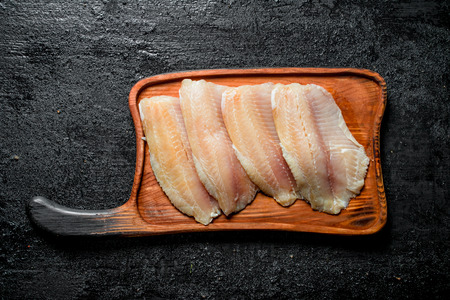 Fish fillet on a wooden cutting Board. On black rustic background 版權商用圖片