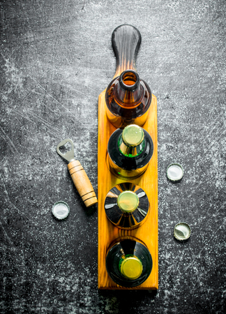 Beer bottles on a stand and opener. On black rustic background