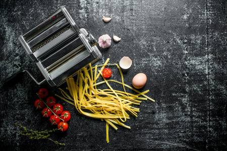 Preparation of homemade raw pasta with tomatoes and thyme. On rustic background