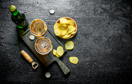 Beer in glasses on the cutting Board and chips in the bowl. On black rustic background Reklamní fotografie