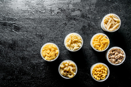 Variety of dry pasta in bowls. On black rustic background