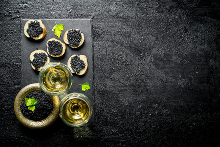 Sandwiches with black caviar and caviar in a bowl with wine in glasses. On black rustic background