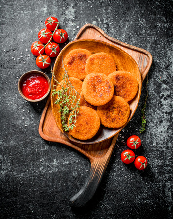Fish cutlets on a plate with thyme,tomatoes and sauce. On black rustic background 版權商用圖片
