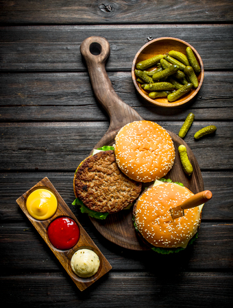 Burgers on a cutting Board with a knife and gherkins in a bowl. On black wooden background 版權商用圖片