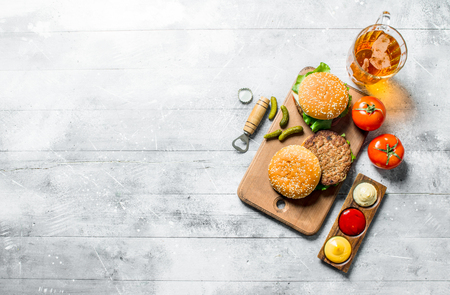Burgers with beer,tomatoes and different sauces. On white wooden background