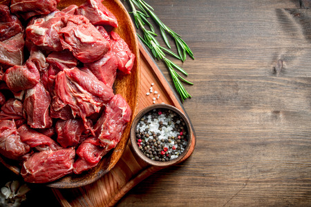 Sliced raw beef on a plate with rosemary and seasonings in a bowl. On wooden background Reklamní fotografie