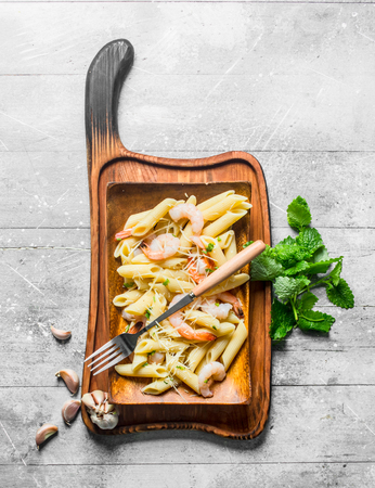 Pasta with shrimp, mint leaves and garlic slices. On white wooden background