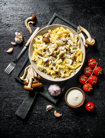 Fusilli pasta with mushrooms, tomatoes and garlic. On black rustic background
