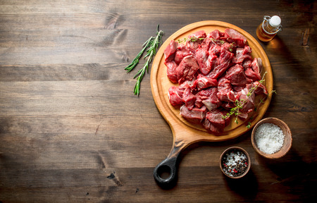 Cut raw beef with thyme,rosemary and butter. On wooden background