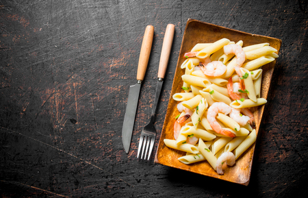Pasta with shrimp on a wooden plate with a knife and fork. On dark rustic background 版權商用圖片