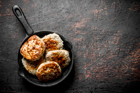 Cutlets in pan. On dark rustic background