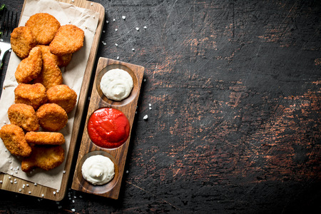 Chicken nuggets and different sauces. On dark rustic background