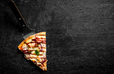A piece of fragrant barbecue pizza. On black rustic background
