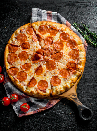 Sliced pepperoni pizza with rosemary and tomatoes. On rustic background Standard-Bild